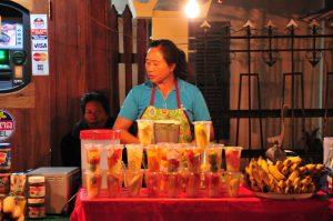 Obst Verkäuferin in Laos mit mundgerecht geschnittenem laotischen Obst in Plastikbechern auf dem Nachtmarkt in Vientiane auf einer Laos Reise