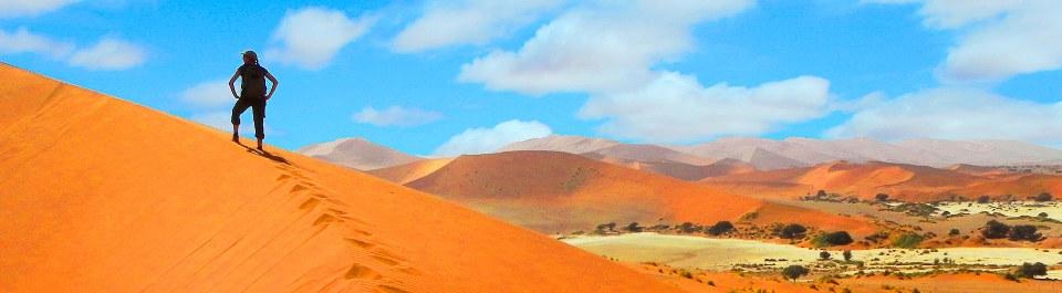 Reisegast wandert auf eine Sanddüne im Sossusvlei in Namibia