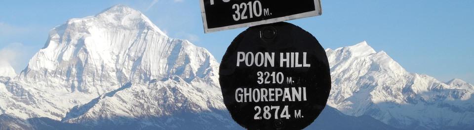 Blick auf den schneebedeckten Poon Hill in Nepal mit einem Wegweiser im Vordergrund