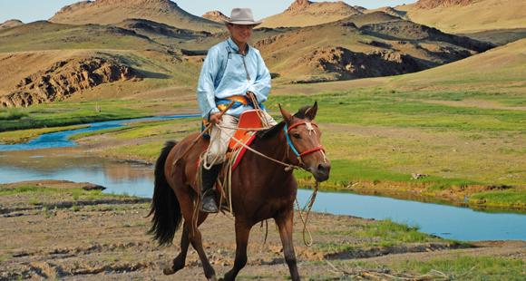 Mongolischer Nomade mit Pferd an einem Fluss in der Mongolei in der Nähe des Ongii Klosters auf einer Mongolei Reise