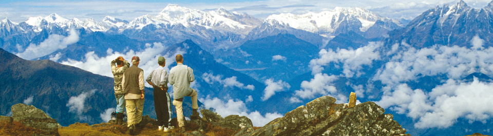 Vier Wanderer blicken von einem Aussichtspunkt auf das Langtang Tal während einer Nepal Reise mit schneebedeckten Eisriesen des Himalaya Gebirges am Horizont