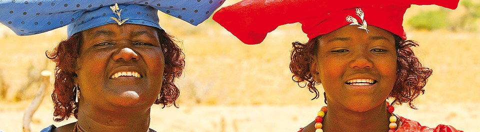 Lachende Herero Frauen mit traditioneller Kopfbedeckung