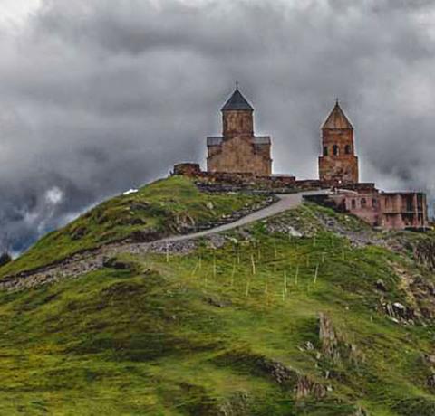 Gergetier Dreifaltigkeitskirche in Georgien vor einer Landschaft aus Bergen mit Wolken