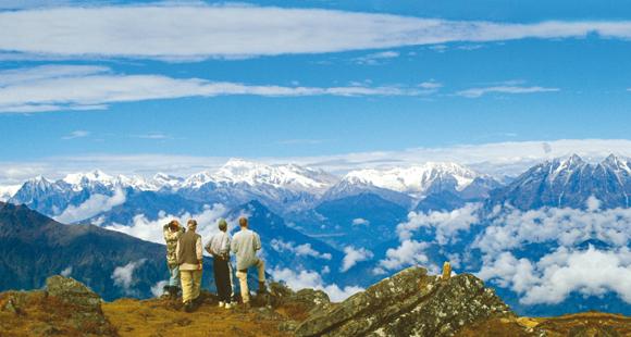 Wanderer stehen auf einem Aussichtspunkt und schauen auf das Langtang Tal in Nepal mit den Bergen des Himalaya am Horizont