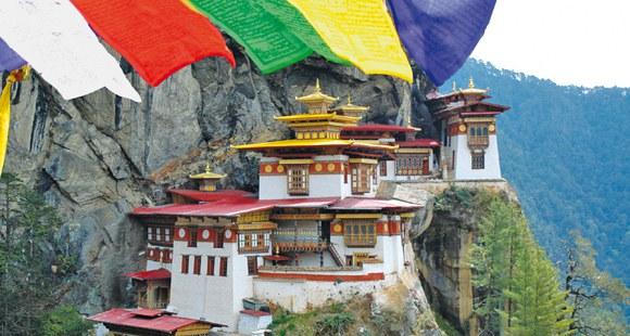 An den Berg geschmiegtes Tigernest Kloster in Bhutan mit Gebetsfahnen im Vordergrund