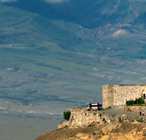Ausblick auf das Khor Virap Kloster in Armenien, im Hintergrund Berge mit Wolken
