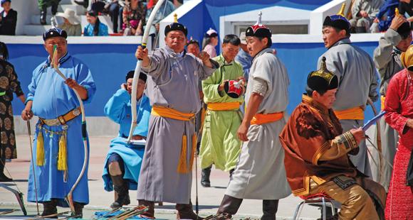 Nomaden beim Bogenschiessen in Ulan Bator auf dem Naadam Fest während einer Mongolei Reise.