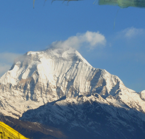Aussicht auf den Poon Hill während einer Nepal Reise mit bunten Gebetsfahnen im Vordergrund