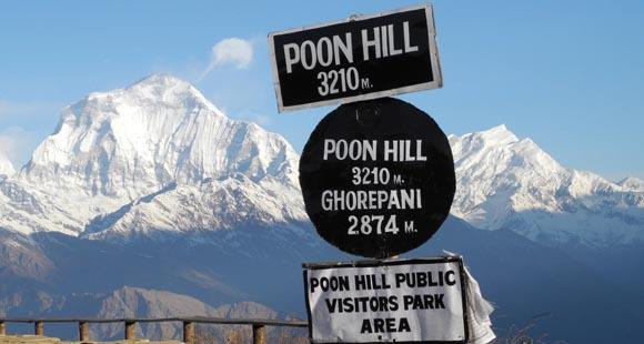 Aussicht auf den schneebedeckten Poon Hill in Nepal mit einem Wegweiser im Vordergrund