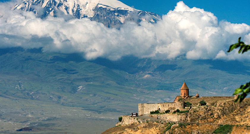 Kloster Khor Virap in Armenien vor verschneiten Bergen mit Wolken