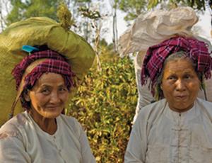 Lachende einheimische Frauen in Myanmar mit Gepäck auf den Köpfen