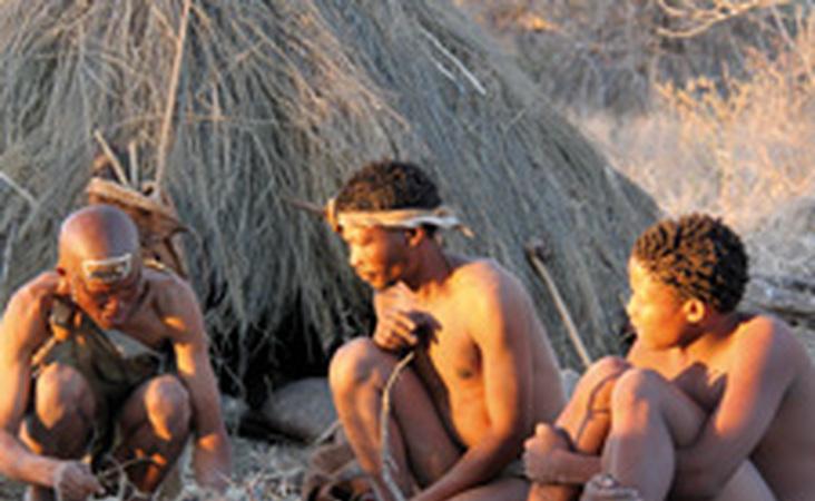 Drei Buschmänner beim Feuermachen in Botswana