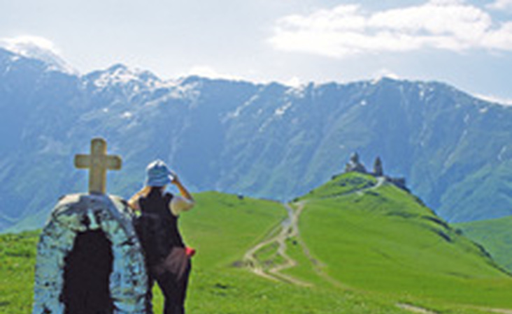Wanderer blickt auf die Gergeti Dreifaltigkeitskirche in Georgien