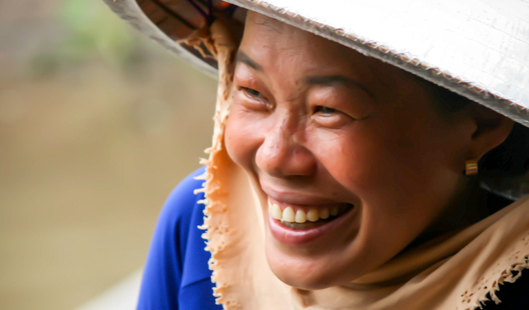 Lachende Vietnamesin mit traditionellem Hut