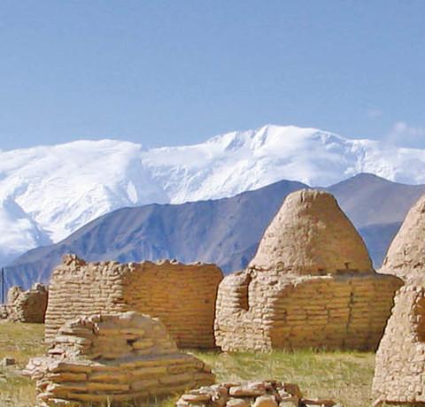 Grabtürme in Kirgistan und im Hintergrund schneebedeckte Berge