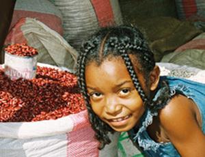 Mädchen neben einem Gewürzsack in Madagaskar