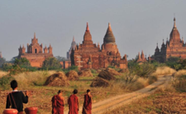 Tempel in Bagan mit drei Mönchen und einem Träger im Vordergrund in Myanmar