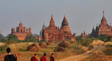 Tempelanlagen von Bagan auf einer Myanmar Reise mit drei Mönchen und einem Träger im Vordergrund