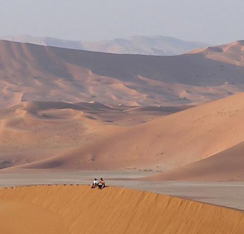 2 Menschen sitzen auf einer Sanddünenkante in der Rub al Khali Wüste auf einer Oman Reise