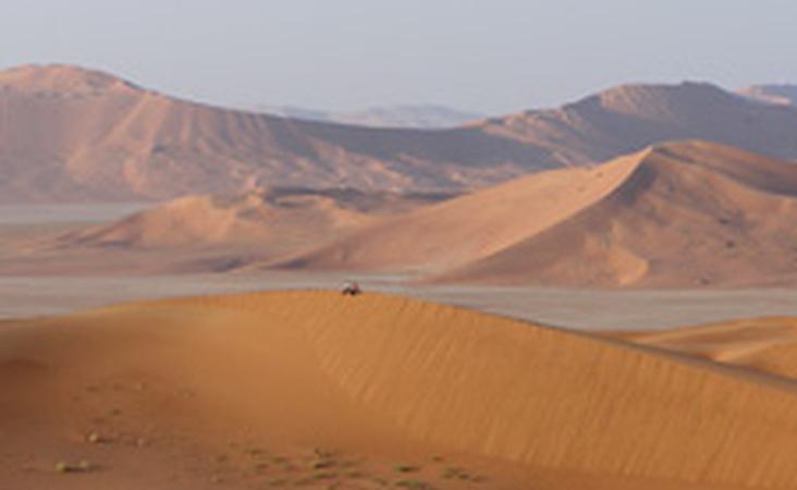 Sanddünen in der Rub al Khali Wüste im Oman mit einem Jeep der in den Dünen parkt